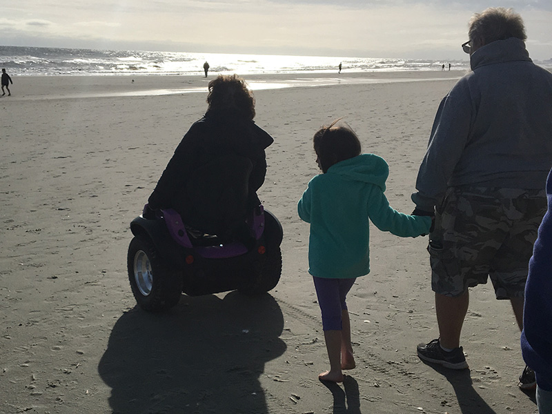 Kim on her Omeo at the beach with her family